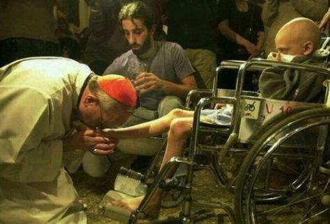 O então Cardeal Bergoglio, agora Papa Francisco, lavando os pés a um pequeno em cadeira de rodas