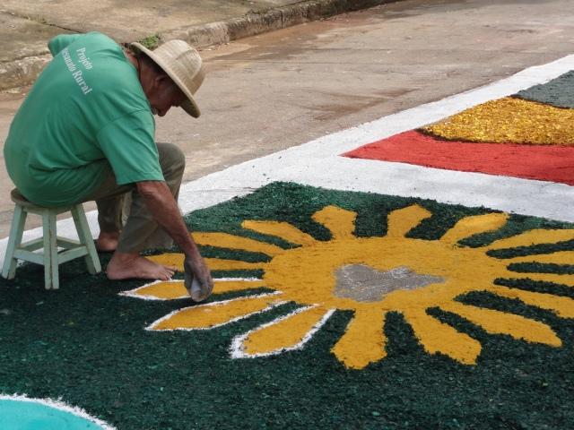 Voluntário faz tapete para a procisão