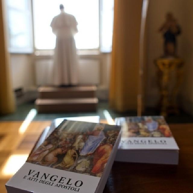Papa Francisco rezando o Angelus deste domingo e em primeiro plano os livros dos Evangelhos distribuídos ao povo.