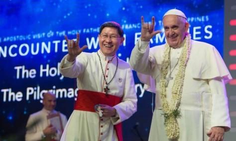 O Papa Francisco e o acerbispo de Manila, Luis Antonio Tagle, cumprimentam público com gesto popular - - / AFP